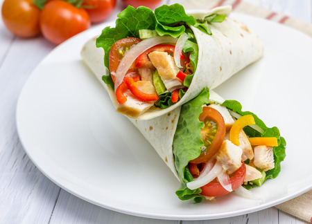 Foto de Tortilla wraps with roasted chicken fillet, fresh vegetables and sauce on white plate - Imagen libre de derechos