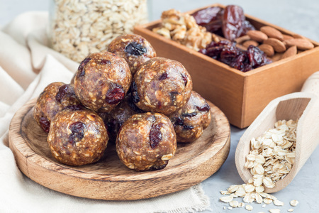 Photo for Healthy homemade energy balls with cranberries, nuts, dates and rolled oats on a wooden plate, horizontal - Royalty Free Image