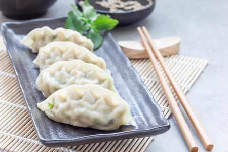Foto de Steamed Korean dumplings Mandu with chicken meat and vegetables on a black plate, horizontal, copy space - Imagen libre de derechos