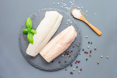 Photo for Fresh raw cod fillet with spices, pepper, salt, basil on a stone plate, horizontal, copy space, top view - Royalty Free Image