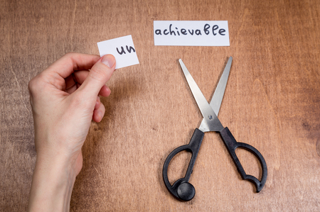 Photo pour The word unachievable cut with scissors. Self motivation concept - image libre de droit