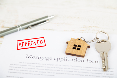 Photo pour Approved mortgage loan agreement application with a house shaped keyring - image libre de droit