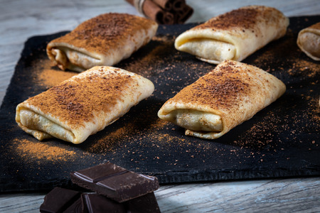 Photo for Pancakes covered with cinnamon and chokolate  crumbs on black desk. - Royalty Free Image