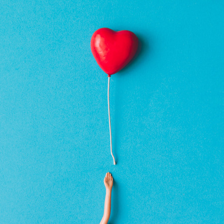 Photo for Doll hand with heart shaped baloon. Minimal concept. Flat lay. - Royalty Free Image