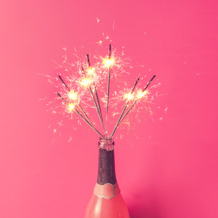 Photo for Champagne bottle with sparklers on pink background. Flat lay. - Royalty Free Image