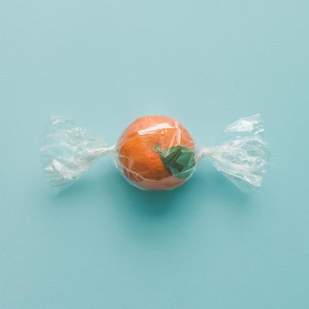 Photo pour Orange wrapped like candy on bright blue background. minimal food concept. - image libre de droit