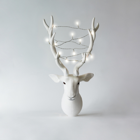 Foto de White Christmas reindeer head with antlers with christmas lights. New Year concept. - Imagen libre de derechos