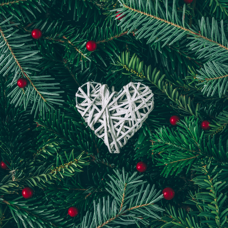 Photo pour Creative layout made of Christmas tree branches with heart decoration. Flat lay. Nature New Year concept. - image libre de droit