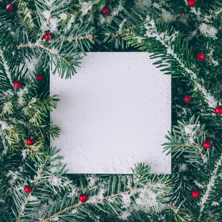 Foto de Creative layout made of Christmas tree branches with snow and paper card note. Flat lay. Nature New Year concept. - Imagen libre de derechos