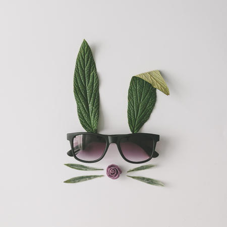 Photo pour Bunny rabbit face made of natural green leaves with sunglasses on bright background. Easter minimal concept. Flat lay. - image libre de droit