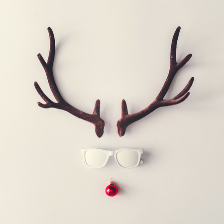 Photo pour Santas reindeer made of antlers, white sunglasses and red New Year bauble decoration. Minimal winter holiday concept. - image libre de droit