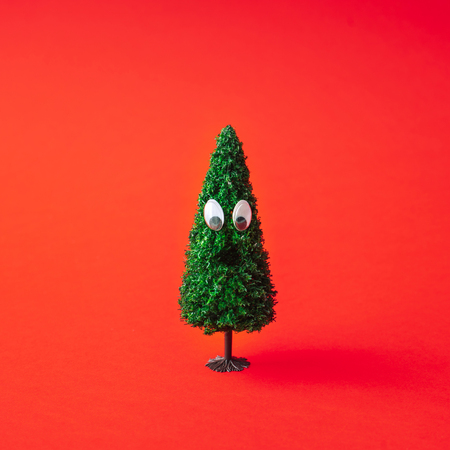 Photo for Christmas tree with googly eyes on red background. Minimal New Year fun concept. - Royalty Free Image