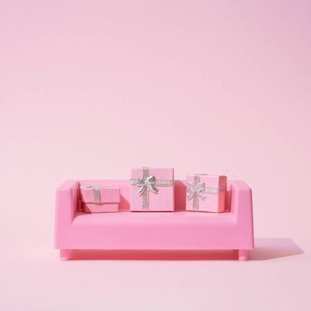 Photo for Christmas composition. Pink sofa, with presents on pink background. Christmas holidays, new year minimal concept. - Royalty Free Image