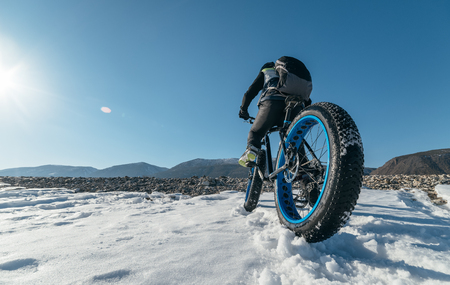 Photo for Fatbike (also called fat bike or fat-tire bike) - Cycling on large wheels. Teen rides a bicycle through the snow mountains in the background. - Royalty Free Image