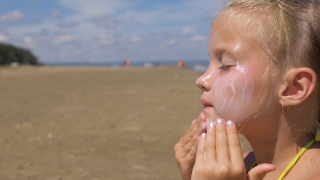 Foto de The girl apply sunscreen to face and body. The girl squeezes the sunscreen into her palm and puts it on her face. - Imagen libre de derechos