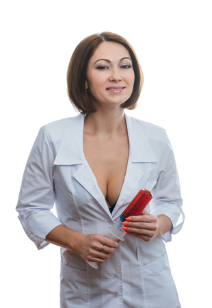 Foto per Sexually doctor woman on isolated white background. Caucasian woman medic with beautiful sexy pantyhose, bra and panties. The girl has a big syringe with a red liquid. - Immagine Royalty Free