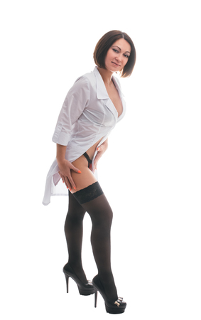 Foto de Sexually doctor woman on isolated white background. Caucasian woman medic with beautiful sexy pantyhose, bra and panties. The girl has a big syringe with a red liquid. - Imagen libre de derechos
