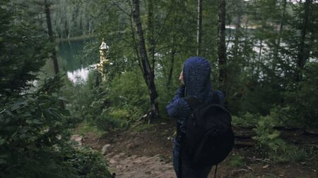 Photo pour Traveler photographing scenic view in forest. One caucasian woman shooting nice magic look. Girl take photo video on dslr mirrorless camera. Professional photographer travel with backpack. Outdoor. - image libre de droit