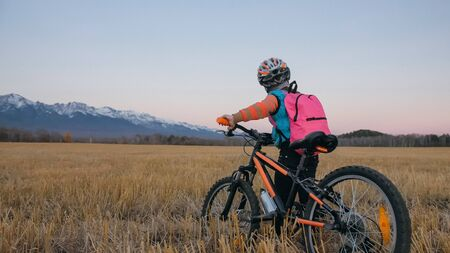 Foto de One caucasian children walk with bike in wheat field. Little girl walking black orange cycle on background of beautiful snowy mountains. Biker stand with backpack and helmet. Mountain bike hardtail. - Imagen libre de derechos
