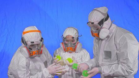 Foto de Family of doctors scientists health worker in respirator. Mom, dad and daughter portrait, wearing protect medical aerosol spray paint mask. Ball spike model Coronavirus pandemic covid-19. - Imagen libre de derechos