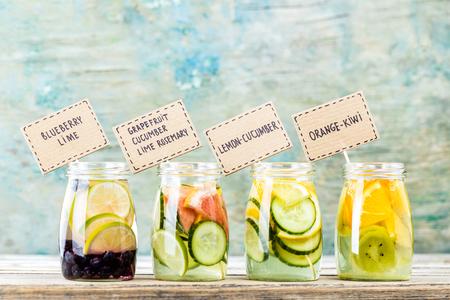 Foto de Variety of fruit infused detox water in jars for a healthy diet - Imagen libre de derechos