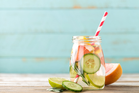 Foto de infused detox water with lime, grapefruit, cucumber and rosemary for diet healthy eating and fat burning with space for a text - Imagen libre de derechos