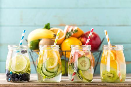 Foto de Variety of fruit infused detox water in glass jars for a healthy diet eating - Imagen libre de derechos