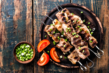 Photo pour Grilled meat skewers, shish kebab on wooden background, top view - image libre de droit