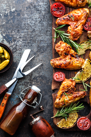 Foto de appetizing chicken wings grilled barbecue with spices and vegetables until crispappetizing chicken wings grilled barbecue with spices and vegetables until crisp, top view, space for text - Imagen libre de derechos