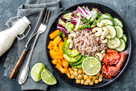 Foto de Vegetarian salad Buddha bowl dish with brown rice, avocado, pepper, tomato, cucumber, chickpea, chia seeds, fresh lettuce salad and cashew nuts. Healthy eating trend, superfood. Top view - Imagen libre de derechos