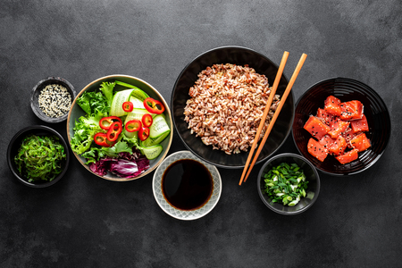 Foto de culinary background of poke bowl ingredients - brown rice, trout or salmon fillet, Chuka Seaweed Salad, sesame and fresh vegetables, top view, copy space, healthy food background - Imagen libre de derechos