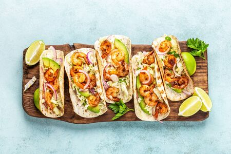 Photo for Shrimp tacos. Seafood fajitas with cabbage, onion, parsley in tortillas served on wooden cutting board - Royalty Free Image