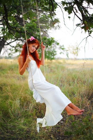 The red-haired girl in a white dress shakes on a swing in a grove