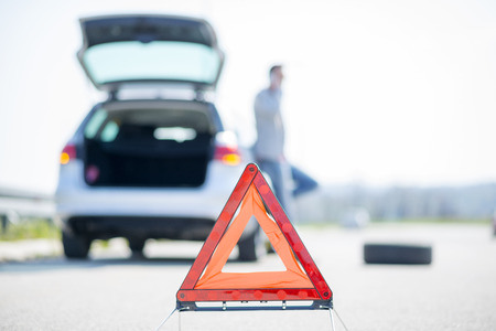Foto de A young man with a silver car that broke down on the road.He has set up a warning triangle.He is waiting for the technician to arrive. - Imagen libre de derechos