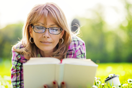 Photo for Woman reading outdoors.Happy woman reading a book during springtime in nature. - Royalty Free Image