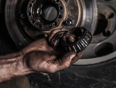 Photo pour Dirty man hand with gear and car wheel - image libre de droit