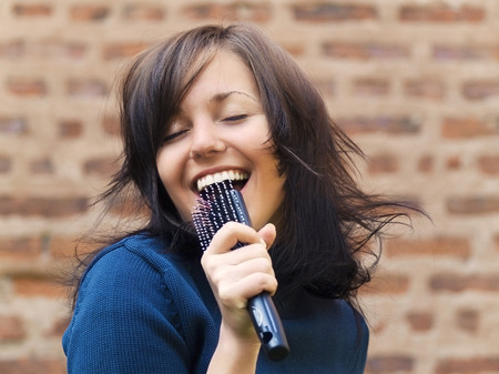 Photo for Young tousle-headed brunette pretending to sing with her hair brush as a microphone - Royalty Free Image