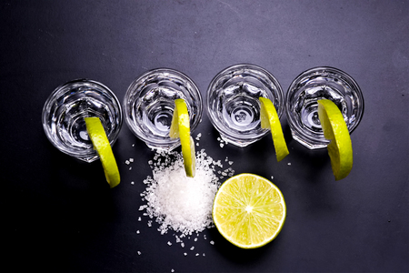 Foto de Glasses of silver and gold tequila with lime in a bar - Imagen libre de derechos
