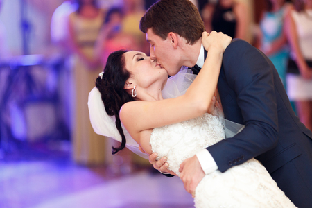 Photo pour Groom kisses a bride bending her over during their first dance - image libre de droit