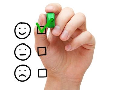 Foto de Hand putting check mark with green marker on customer service evaluation form. - Imagen libre de derechos