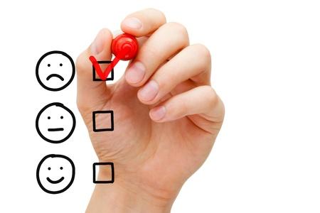 Foto de Hand putting check mark with red marker on poor customer service evaluation form. - Imagen libre de derechos