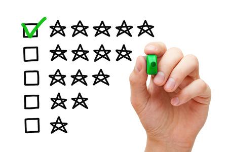 Foto de Hand putting check mark with green marker on five star rating. - Imagen libre de derechos