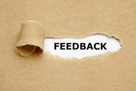 Foto de The word Feedback appearing behind torn brown paper. - Imagen libre de derechos