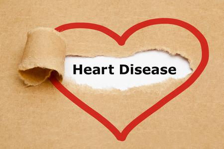 Foto de The text Heart Disease appearing behind torn brown paper. - Imagen libre de derechos