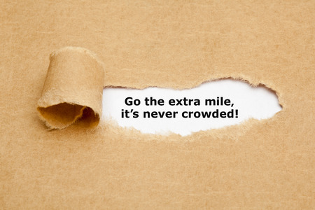Photo for Motivational quote Go The Extra Mile It's Never Crowded appearing behind ripped brown paper. - Royalty Free Image
