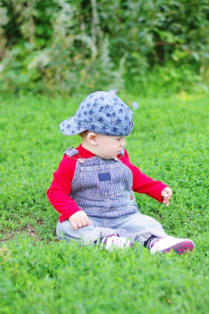 baby age of 10 months plays sitting on grass in park