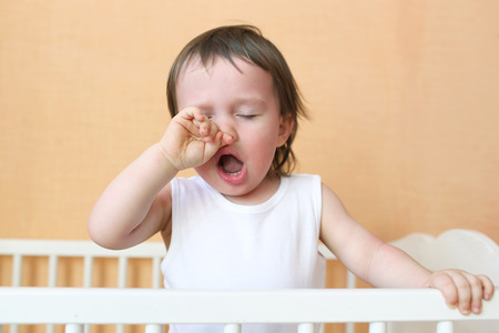 Photo for yawning baby age of 18 months in white bed - Royalty Free Image