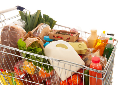 Photo pour Shopping cart full with dairy grocery products isolated over white background - image libre de droit