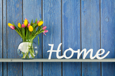 Photo for Home in white letters with colorful bouquet tulips in pink and yellow isolated on background - Royalty Free Image
