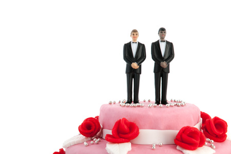 Photo pour Pink wedding cake with red roses and gay couple on top - image libre de droit